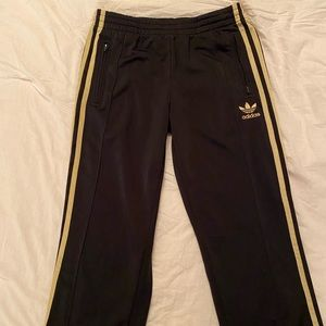Adidas track pants with gold stripes